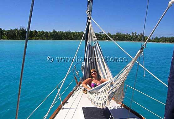 Solar sig i en hängmatta upphängd på båt
