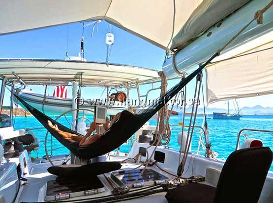 Gungar skönt i en hängmatta upphängd i skuggan på en båt