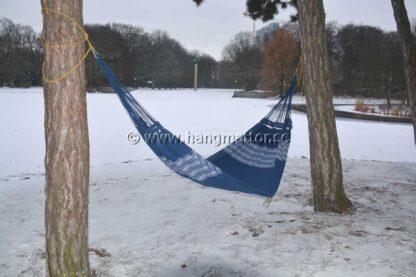 Hängmatta Búzios upphängd i snö mellan träd på vintern