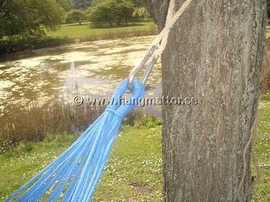 Upphängning av hängmatta med karbinhakar och rep mellan träd
