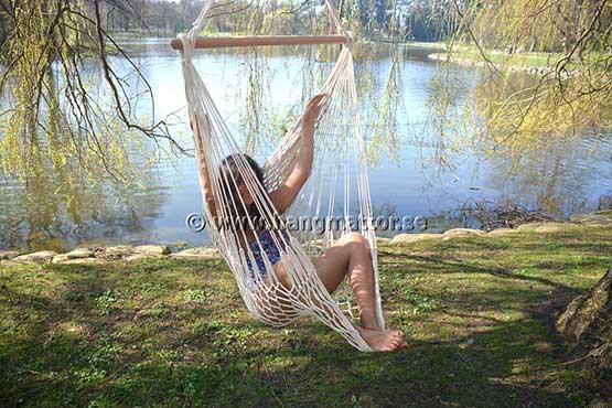 Sitter i hängstol med benen uppe