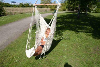 Sittande i hängstol med fotstöd med ben till vänster